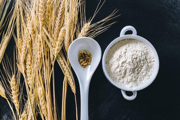 Wheat ears and flour on black