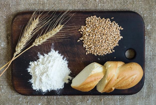 解任の背景にあるキッチンボード上の小麦の穂、穀物、小麦粉、スライスされたパン。上面図