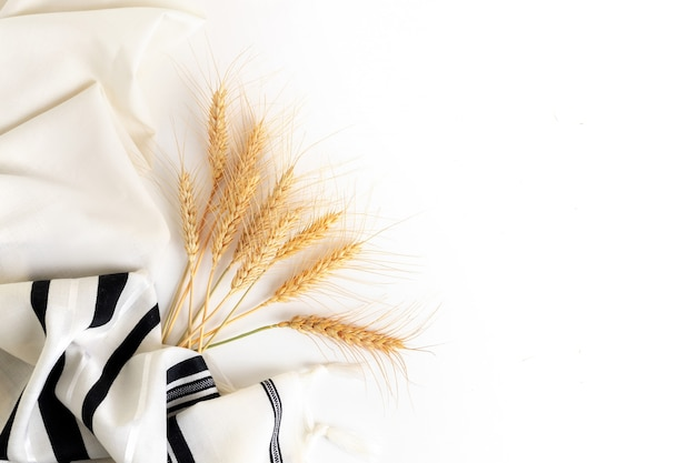 Wheat ears and tallit on white background