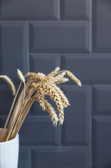 Wheat ears in a white ceramic vase against grey brick wall straws or dry plants