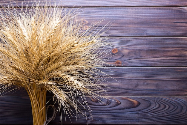 Wheat ears on wooden background