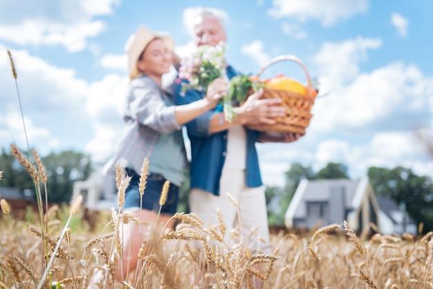 小麦畑。夏の日に麦畑の真ん中に立っている間、休息と安心を感じて晴れやかな愛情のあるカップル