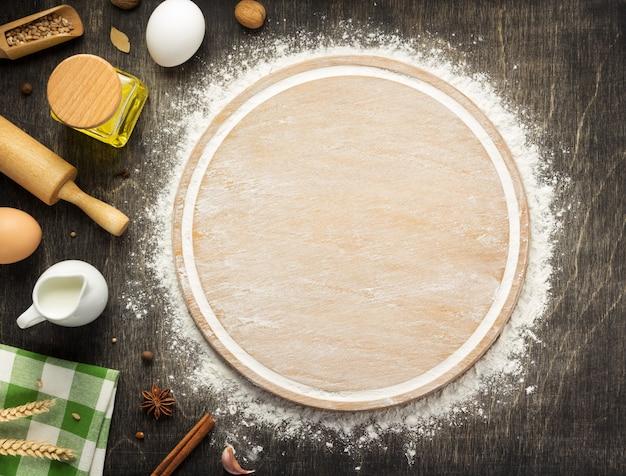 木製の背景、上面図に小麦粉とまな板