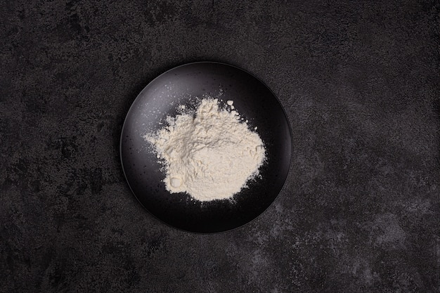 Wheat flour in a black plate on a dark background. the ingredient. bakery products. copyspace
