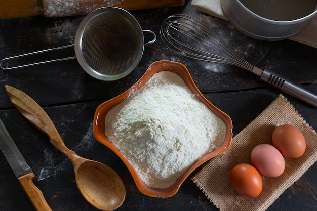 Wheat flour in a ceramic dish and chicken eggs for the dough preparation.