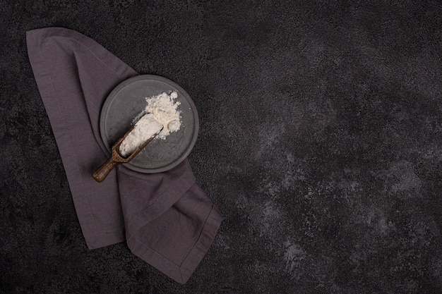 Wheat flour in a concrete plate on a dark background. the ingredient. bakery products.