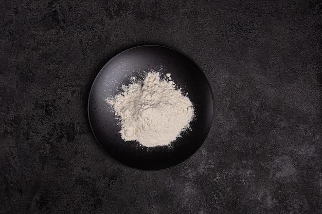 暗い背景の上の黒いプレートの小麦粉。材料。ベーカリー製品。コピースペース