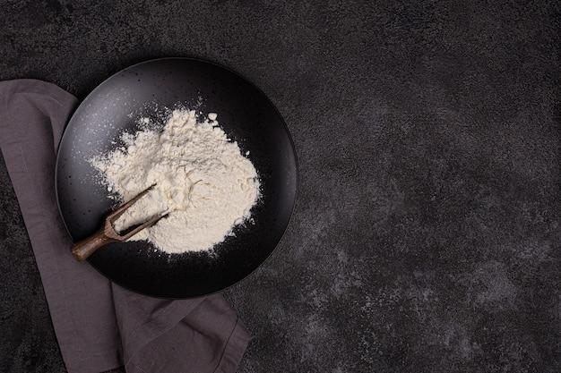 暗い背景の上の黒いプレートの小麦粉。材料。ベーカリー製品。
