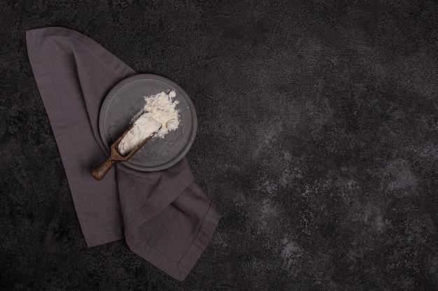 暗い背景のコンクリートプレートに小麦粉。材料。ベーカリー製品。