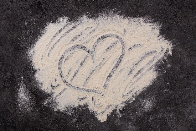 暗い背景に小麦粉が散らばっている材料ベーカリー製品