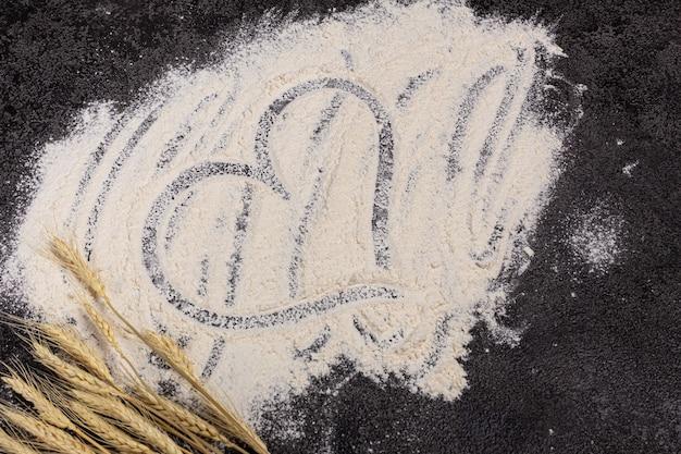 暗い背景に小麦粉が散らばっている成分ベーカリー製品料理の始まり