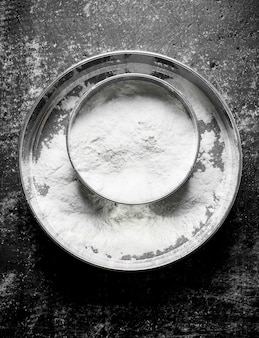 Wheat flour sieve on rustic table.