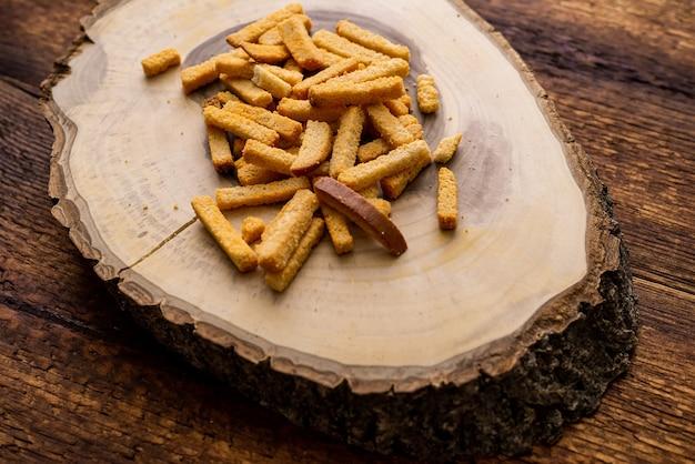 나무 배경에 밀 튀긴 croutons입니다. 나무 조각으로 만든 접시에 간식.