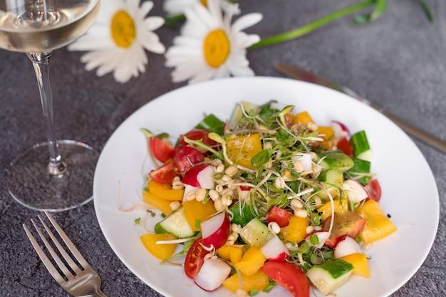 밀 배아 샐러드, 토마토, 고추, 무, 오이, 올리브 오일. 회색 배경에 흰색 접시에 야채 샐러드입니다.