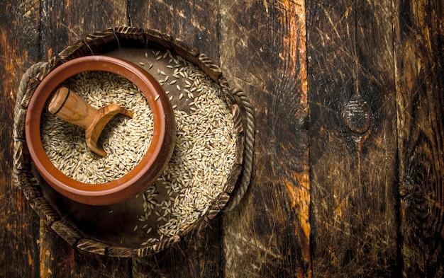 木製の背景にスクープとボウルに小麦粒