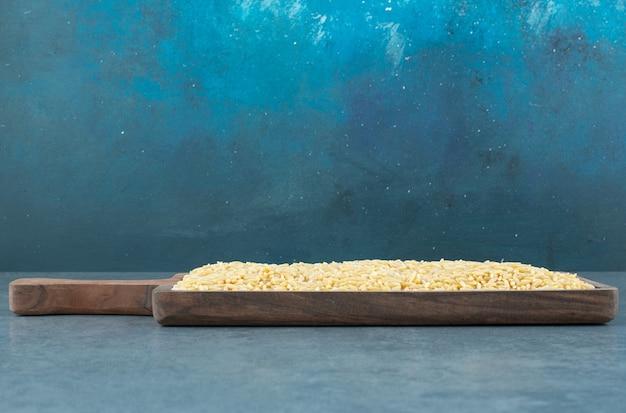 Зерна пшеницы аккуратно сложены на деревянной доске на синем фоне. фото высокого качества
