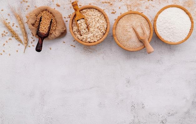 白いコンクリートの背景に設定された木製のボウルに小麦粉、茶色の小麦粉と白い小麦粉。