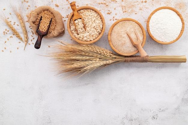 밀 곡물, 갈색 밀가루와 나무 그릇에 흰 밀가루는 흰색 콘크리트 배경에 설정합니다.