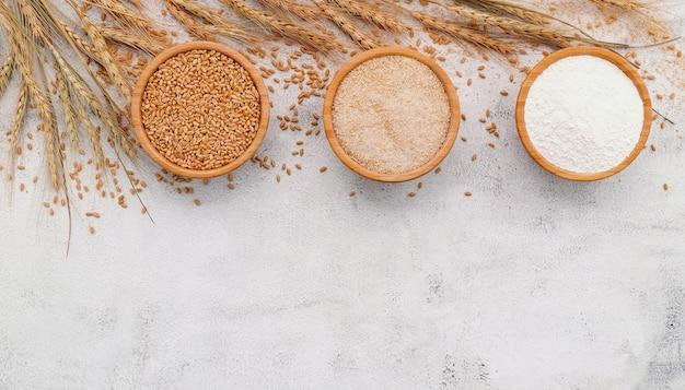 Зерна пшеницы, коричневая пшеничная мука и белая пшеничная мука в деревянной миске на белой конкретной предпосылке.