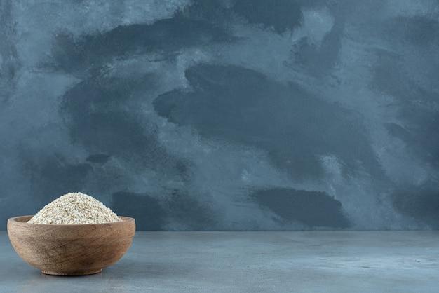 青い背景の上の木製のカップの小麦粒。高品質の写真