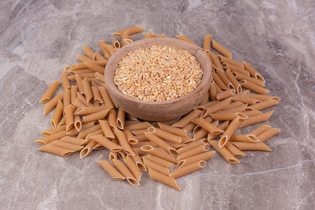 パスタが周りにある木製のカップの小麦粒