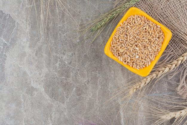 オレンジ色のセラミックカップの小麦粒。