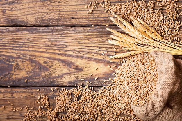 木製のテーブルの上の袋の小麦粒