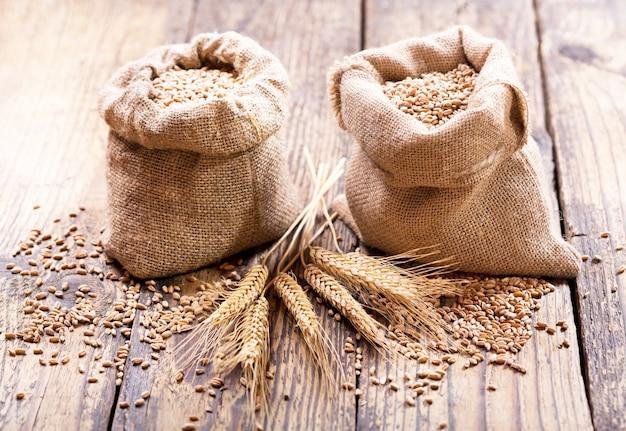 木製のテーブルの袋の小麦粒