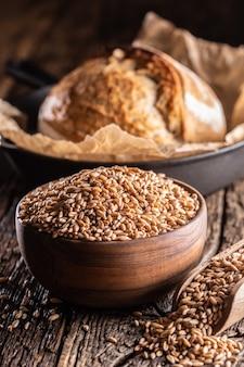 밀 알갱이 - 빵의 주재료는 나무 그릇과 소박한 나무 국자에 채워져 있습니다. 바삭한 빵을 backround에 굽습니다.