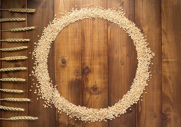 Wheat grains on wooden background, top view