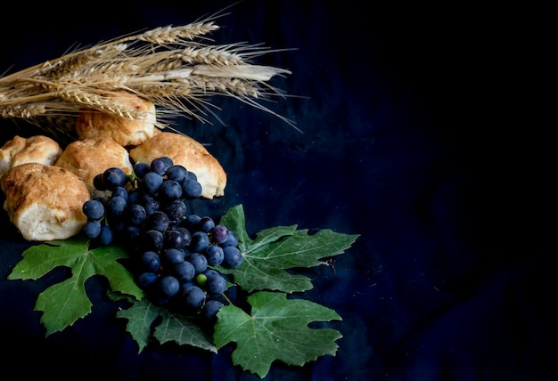 Wheat grapes bread and crown of thorns on black background