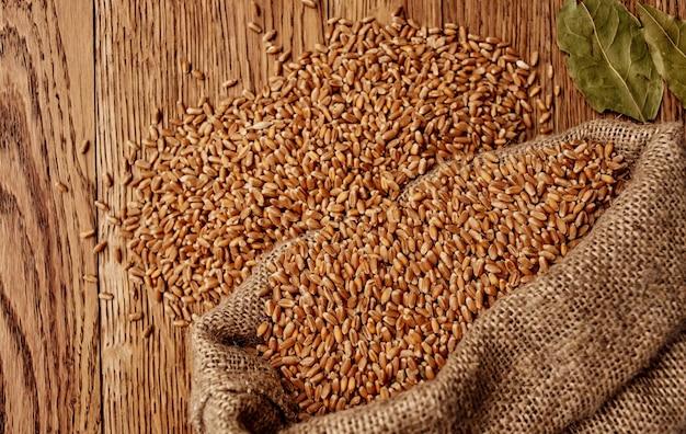 木製のテーブルと乾燥した葉の有機的な質感の背景画像の上の袋に小麦