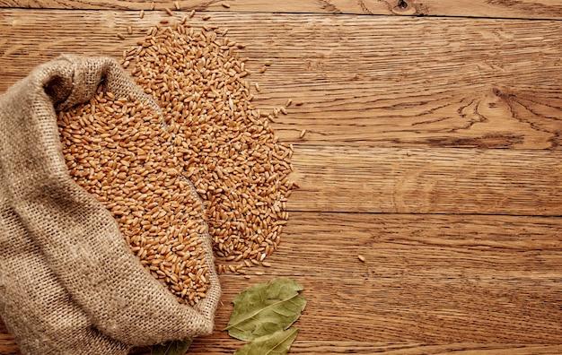 Пшеница в сумке на деревянном столе и изображение стены текстуры сухих листьев органическое.