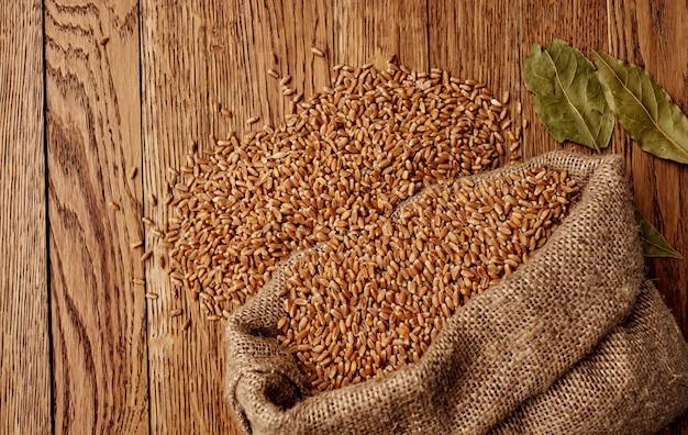 木製のテーブルの上の袋に小麦と乾燥した葉の有機的な質感