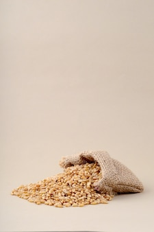 Пшеница в малом мешке на предпосылке, конце вверх.