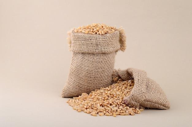 背景の小さな袋に小麦、クローズアップ。