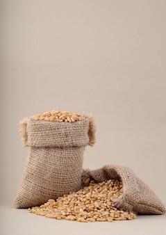 Пшеница в небольшой мешок на столе, крупным планом.