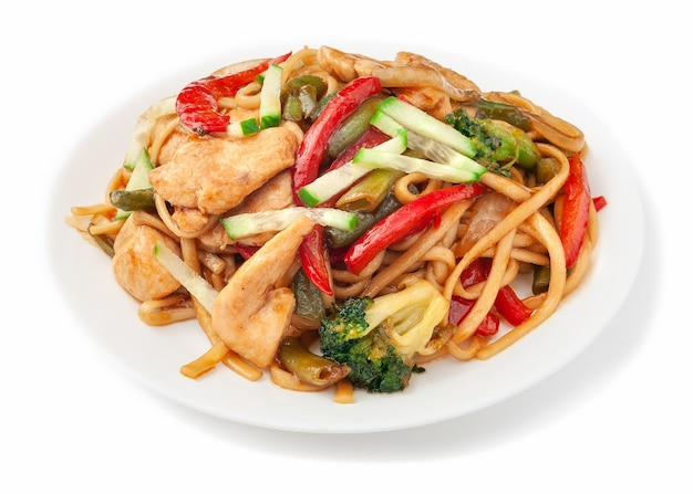 밀 국수 - 닭고기, 파, 강낭콩, 파프리카, 브로콜리, 오이, 우나기 소스를 곁들인 우동. 하얀 접시에. 흰색 배경. 격리.