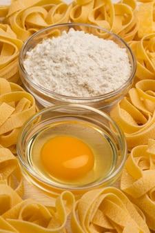 白い背景の上の小麦パスタ、小麦粉、生卵。
