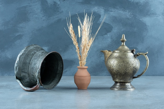 Wheat plant with ethnic metallic pot and kettle around. high quality photo
