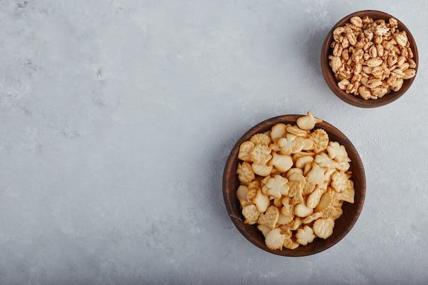 Popcorn e cracker di grano in una ciotola di legno sulla superficie di pietra, vista dall'alto.