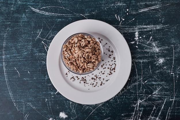 Popcorn di frumento nella tazza di vetro in un piatto bianco.