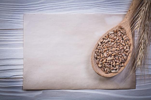 Колосья пшеничной ржи, зерно на деревянной ложке и старинная бумага на деревянной доске