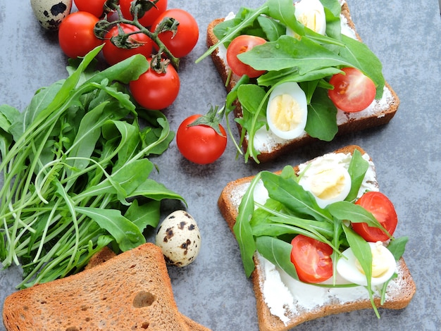 Wheat rye toasts with arugula, quail eggs and cherry tomatoes.