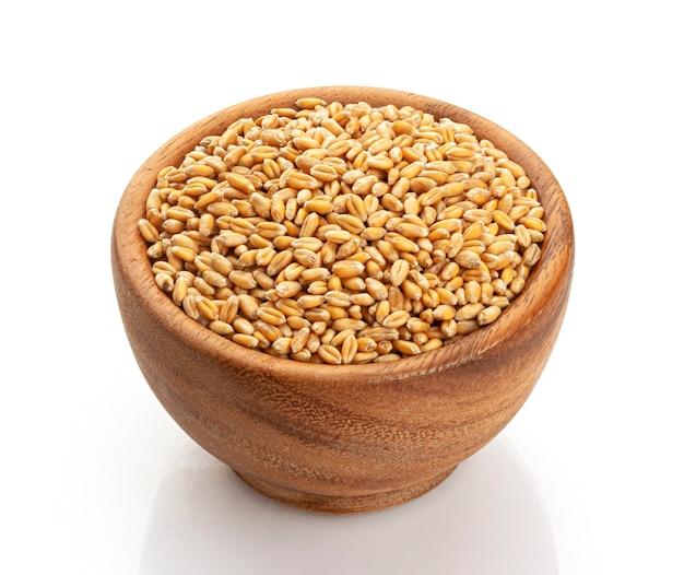 白いテーブルで隔離の木製ボウルの小麦の種子 Premium写真