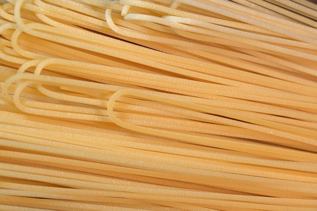 Wheat spaghetti long light yellow raw lie in the kitchen close-up
