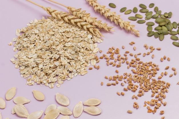 小麦の小穂とオーツ麦のフレーク。テーブルの上のカボチャの種と小麦の粒。フラットレイ。ピンクの背景