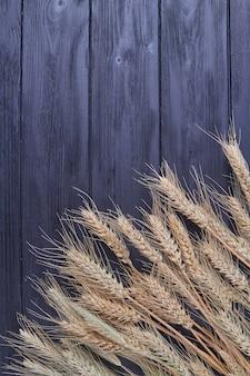 Колоски пшеницы на черном деревянном фоне с копией пространства