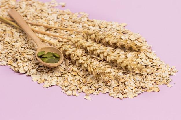 オートミールの小麦小穂。木のスプーンでカボチャの種。フラットレイ。ピンクの背景