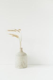 白の木製の花瓶に小麦のスパイクの花束。最小限の花の組成。